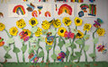 Preschool art projects on display in a classroom depict sunflowers and rainbows Royalty Free Stock Photography