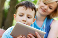 Preschool boy playing on tablet with mother nature Royalty Free Stock Photo