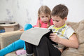 Preschool Caucasian kids having fun with pad while sitting on sofa in domestic room Royalty Free Stock Photo