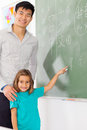 Preschool chinese language girl with teacher pointing answer on chalkboard Stock Images