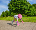 Preschool girl falling down with inline roller skates on Royalty Free Stock Image