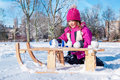 Preschool girl making snowballs sitting beside sledges and Royalty Free Stock Photography