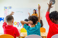 Preschool kid raise arm up to answer teacher question on whiteboard in classroom,Kindergarten education concept Royalty Free Stock Photo