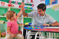 Preschool teacher and child giving high-five Royalty Free Stock Photo