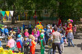 Preschool teacher entertain children in suits of buffoons at the moscow june festival Royalty Free Stock Photography