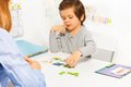 Preschooler boy and developing game with card plays in at the table colorful matching cards his parent indoors Stock Photos