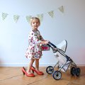 Preschooler girl playing with doll and pram happy little child cute blonde toddler wearing beautiful dress red mom s shoes role Stock Photos