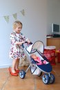 Preschooler girl playing with doll and pram happy little child cute blonde toddler wearing beautiful dress red mom s shoes role Royalty Free Stock Image