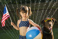 Preschooler holding us flag and beachball posing with dog water coming out of sprinkler in backyard on background Royalty Free Stock Photos