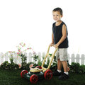 Preschooler mowing an adorable standing on grass with his toy lawnmower the grass is edged by a short fence and foliage on a white Royalty Free Stock Photos