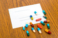 Prescription with colorful pills on wooden ground Royalty Free Stock Photo