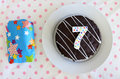 Present and chocolate birthday cake for a seventh birthday or an Royalty Free Stock Photo