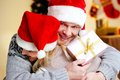 Present for christmas portrait of happy men with giftbox embracing his joyful wife on xmas day Stock Photography