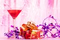 Present spirit cocktail glass with alcohol cocktail christmas decoration and red small with gold ribbon Stock Images