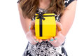 The present is for you closeup of woman holding yellow gift box with black bow Stock Photos