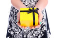The present is for you closeup of woman holding yellow gift box with black bow Royalty Free Stock Image