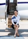 Presentadora de aire sitting on ladder del jet privado Foto de archivo