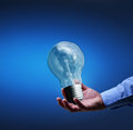 Presenting a new idea businessman hand with old lightbulb Stock Image