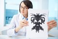 Presenting rorschach inkblot serious psychologist showing paper with Stock Photography