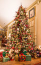 Presents Under Decorated Christmas Tree in Den Royalty Free Stock Photo
