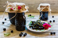 Preserved homemade black currant jam in glass jars on light wooden table. Fresh berries and green leaves, white vintage plate Royalty Free Stock Photo