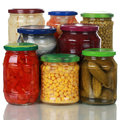 Preserved vegetables in glass jars on white Royalty Free Stock Photography