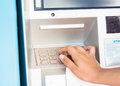 Man`s using the ATM machine with cash cards and entering PIN-pass code on keypad.
