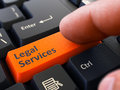 Press button legal services on black keyboard computer user presses orange closeup view blurred background Royalty Free Stock Photo