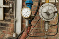 Pressure gauge connected to pipes rusty with brick wall behind Royalty Free Stock Photos