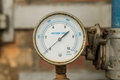 Pressure gauge connected to pipes rusty with brick wall behind Royalty Free Stock Photo