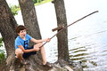 Preteen boy with fishing self made rode handsome on the summer lake background close up photo Stock Photography