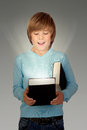 Preteen boy with a lighted book on gray background Stock Images