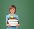 Preteen boy many books green blackboard backgrond Royalty Free Stock Image