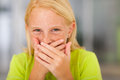 Preteen girl laughing happy covering her mouth and Stock Photos