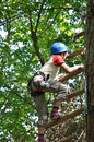 Preteen girl at the obstacle course a is climbing rope ladder high up she is photographed on tree from below Stock Photos