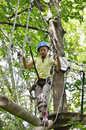 Preteen girl at the obstacle course a is walking on trapeze bar high up he is photographed from below in green forest Royalty Free Stock Photos