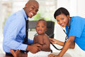 Pretty african female nurse examining little baby boy male doctor Royalty Free Stock Photo
