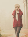 Pretty amazed fashion woman in fur winter hat surprised fashionable fall forest park gorgeous young girl maroon sweater pullover Royalty Free Stock Image