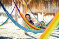 Pretty amazing cheerful young girl on the beach, lying in a hammock and smiling in a black sexy bikini in a wide Royalty Free Stock Photo