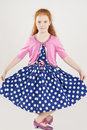 Pretty and artistic caucasian redhaired girl posing in polkadott polkadotted dress standing against white background vertical Stock Photos