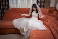 Pretty asian bride joy sit on sofa Royalty Free Stock Photography