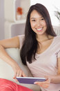 Pretty asian girl using her tablet on the couch smiling at camer camera home in living room Royalty Free Stock Photos