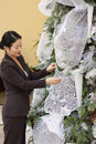 Pretty asian lady trimming crhistmas tree Stock Photography