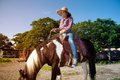 Pretty Asian woman cowgirl riding a horse outdoors in a farm. Royalty Free Stock Photo
