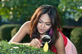 Pretty Asian woman with magnifying glass in the park . Royalty Free Stock Photo