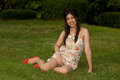 Pretty Asian woman pose of sitting on a lawn in the park . Royalty Free Stock Photo