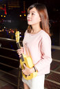 Pretty asian woman with ukelele beautiful malay female city lights in background Stock Photo