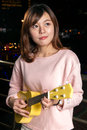 Pretty asian woman with ukelele beautiful malay female city lights in background Stock Image