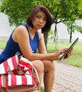 Pretty Asian woman using tablet at the park Royalty Free Stock Photo