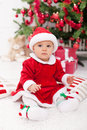 Pretty baby girl in santa costume sitting by the christmas tree Royalty Free Stock Photos